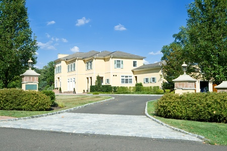 New single family home with gate posts and long driveway in suburban Philadelphia, Pennsylvania.  French Provincial style. Editorial