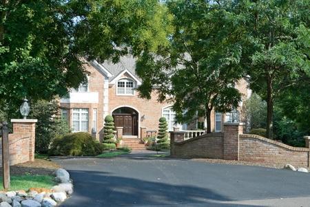 Upscale eengezinswoning met uitgebreide landschapsarchitectuur en de poort in een buitenwijk van Philadelphia, PA. Huis omlijst door bomen.