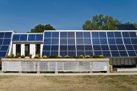 pv: Solar powered home with rows of PV panels on the side and a blue sky in the background. Stock Photo