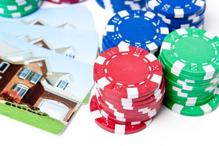 gambling chip: Playing cards with house printed on them next to stacks of poker chips.  Gambling on real estate theme.