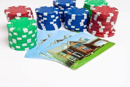 Playing cards with house printed on them next to stacks of poker chips.  Gambling on real estate theme.