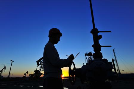 obrero trabajando: Trabajadores del petróleo del yacimiento de petróleo en el trabajo Foto de archivo