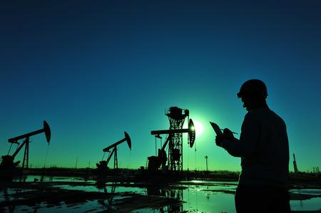 operarios trabajando: Trabajadores del petróleo del yacimiento de petróleo en el trabajo Foto de archivo