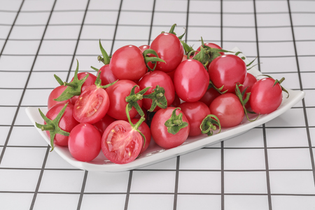 Small red tomatoes in a white plate on a checkered table