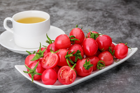A plate of small tomatoes and a cup of tea on the grey table 写真素材