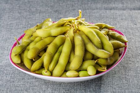 Boiled edamame on a tabletop dish Stock Photo