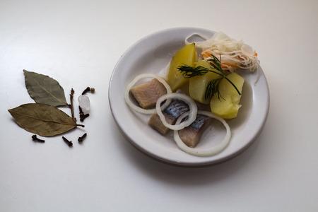 가장 좋아하고 인기있는 러시아 음식은 청어와 양파가 들어간 삶은 감자와 소금에 절인 양배추와 식물성 기름입니다. 접시는 평범한 흰색 접시와 흰색