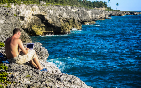 A side view of a man with a bare torso in beige pants and blue slates with a white laptop on his laps seating on a gray cliff on the Southeast coast of the Dominican Republic. Stockfoto