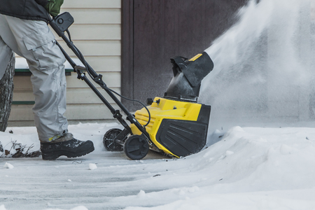 A man in a black jacket and a gray pants is brushing white snow with the yellow electric snow thrower in a winter garden