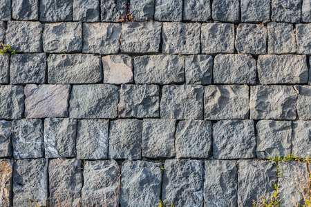 A beautiful horizontal texture of part of an old gray brick wall from frozen volcanic lava from Etna volcano in Sicily in Italy is on the photo.
