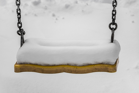 There is a swing painted with yellow paint swings with black metal chains on a children's playground in the courtyard in winter