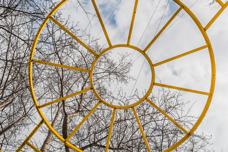 Yellow metal sun against a blue sky with white clouds and poplar tree branches is above the playground