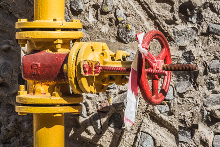 Red metal valve is on a yellow gas pipeline against a gray concrete wall with stones Stock Photo