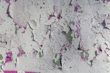 Beautiful horizontal texture of part of shabby old concrete wall painted in white and pink and green blue color with holes is on the photo