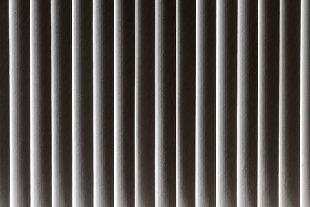 A beautiful horizontal texture of vertical fabric beige blinds shuts the sunlight from the window 版權商用圖片