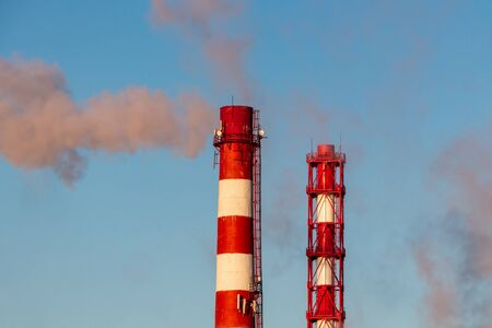 Two red and white chimneys of a boiler with orange smoke are against a blue sky in sunny day
