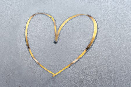 One beautiful bright yellow heart painted by finger on a frozen blue texture on a glass in winter Banque d'images - 134523666