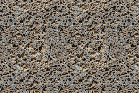 A beautiful texture of orange stone pumice with holes is in the photo