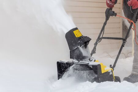 A man is brushing white snow with the yellow electric snow thrower in a winter garden