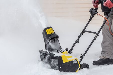 A man is brushing white snow with the yellow electric snow thrower in a winter garden Foto de archivo