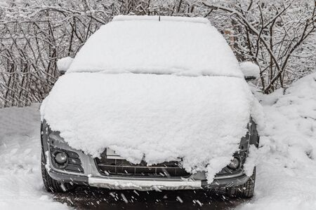 The White fresh snow is on a silver dirty wet car outdoor in winter