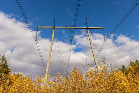 A rusty and black power line is on the blue sky with white clouds background in yellow fields Archivio Fotografico