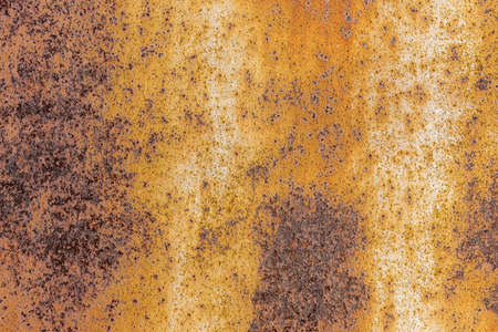 A beautiful horizontal texture of yellow and brown metal sheet with orange rust and holes is in the photo Archivio Fotografico