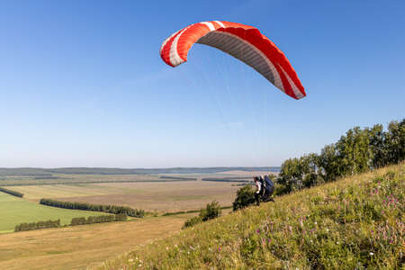 A Beautiful view of a pilot with red and white paraplane going to start flying over the green and yellow fields in the summer morning Banque d'images