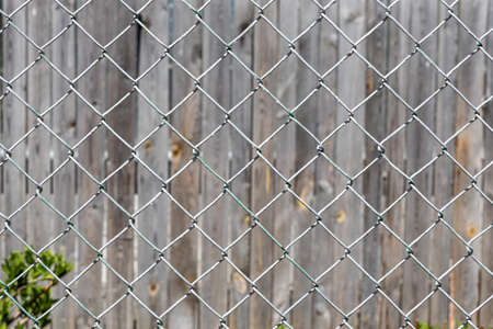 The Texture of Rhombic cells of a white metal lattice is in the sunny day in the summer park on the gray wood background Archivio Fotografico