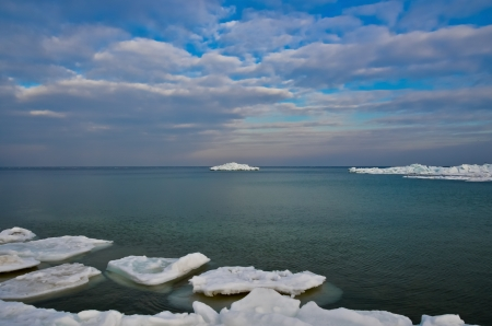 A small iceberg on the horizon against the evening sky and the sea
