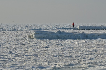 Lonely man on frozen ice sea photo