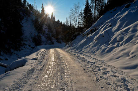 Sunny winter snow road on mountains photo