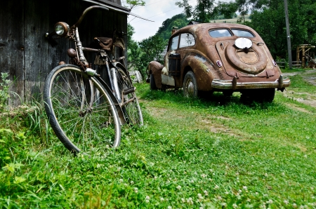 rusty car: Old vintage car and bicycle in the village Stock Photo