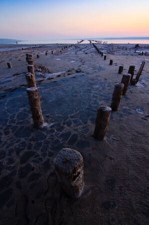 Tidal defences on a beach at dusk with rows of exposed poles to stabilise the sand on the shoreline and prevent tidal erosion against a pretty orange sky