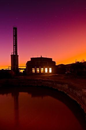 Colourful orange and purple sunset behind a brightly lit factory or industrial building with a steel lattice work tower alongside in silhouette against the sky