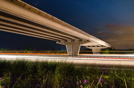 Night bridge to highway road with light trails at the night photo