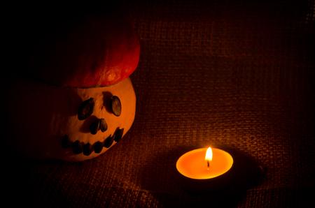 Unusual cheerful Halloween orange hat pumpkin and candle fire  on sackcloth jute background