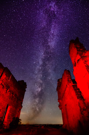 The night sky and the Milky Way and the unusual red light illuminated silhouette of the ruins - the concept of another planet