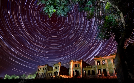 Star trails the night sky against the background of an old tree and a ruined building-  circles of time concept Stock Photo