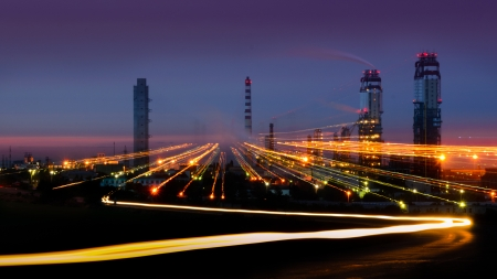 Large industrial plant at night, with smoking chimneys against the light trails of cars  DOF
