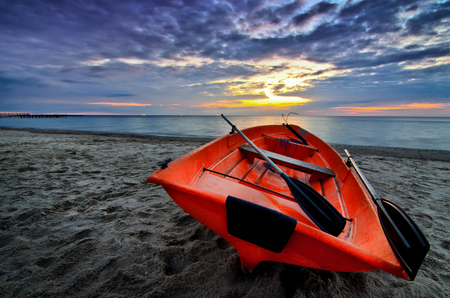 Orange boat on the ocean beach -at dramatic sunrise clouds sky Stock Photo