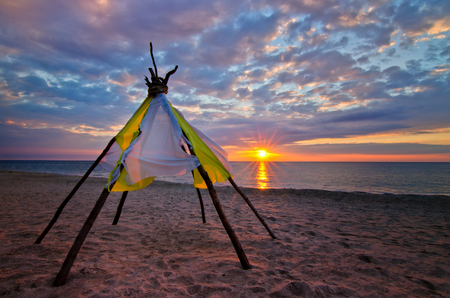 teepee: Wooden wigwam on the shore of the ocean - a colorful sunrise and beautiful clouds