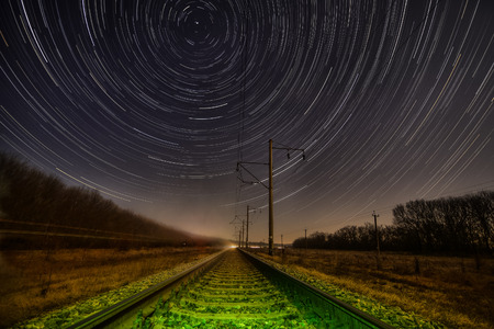 Night rails -green light train way with motion stars, stratrails skyes
