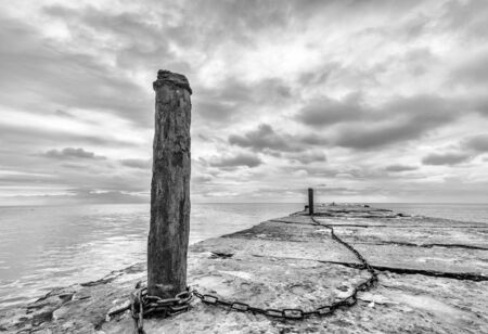 Chained together -old concrete pier with rusty chained poles Stock Photo