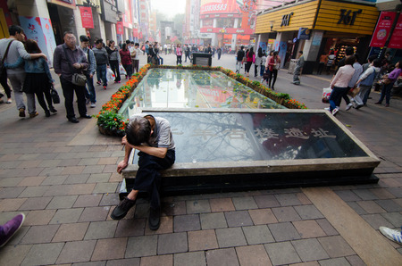 Guangzhou, China - February 29   An unidentified man sits alone  Gini coefficient in China in 2012 amounted to 0,474  The Gini coefficient is used to determine the extent of the income gap between rich and poor, on February 29, 2013, in Guangzhou, China