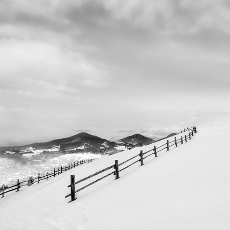 Black fence on white snow on mountains - minimalism concept of calmness photo