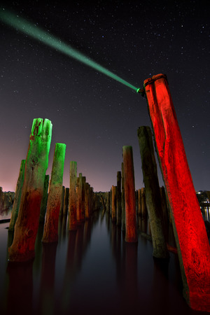 Unusual red poles in the water reflection  at night with deep stars sky photo