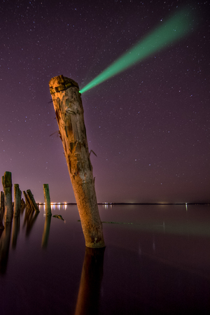 Unusual  pole with beam in the water  at night with deep stars sky photo