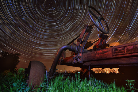 Circles of time  concept - old rusty tractor on star trails night  photo