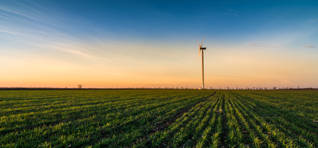 Wind turbine at sunset on green field and clouds blue sky Stock Photo